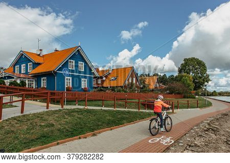 Happy Active Child Riding A Bike On A Bike Path By Sea. Sporty Kid Outdoors. Cycling Through The Cit