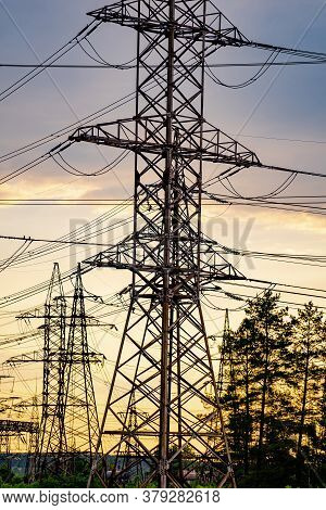 High Voltage Electric Tower. Silhouette On Sunset Time. Power Pylons On Sunset Time Background. Sele