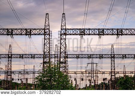 High Voltage Post. High Voltage Pylons Against Sunset Background. Energy And Industrialisation Conce