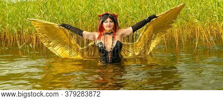 A Woman In The Image Of A Demon In A Black Corset With Golden Wings In The Lake Reeds.
