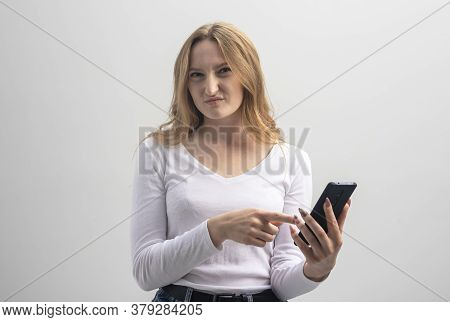 Angry Or Dissatisfied Young Woman Staring At Camera And Showing At Mobile Phone In Disbelief And Ann