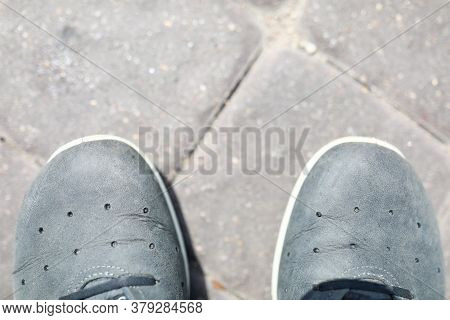 Top View Of Persons Feet In Shoes. Sneakers Covered With Dust. Man Standing On Asphalt Blocks Outdoo