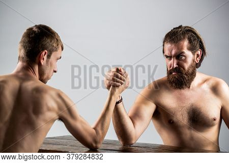 Arm Wrestling. Heavily Muscled Bearded Man Arm Wrestling A Puny Weak Man. Arms Wrestling Thin Hand,