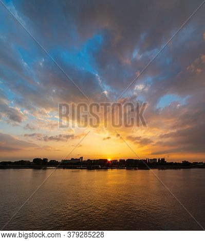 Silhouette Of City On A River At Sunset Under A Majestic Golden Sky With Sun Setting Behind The Buil