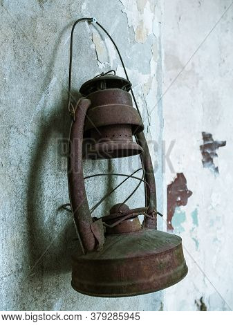 Very Old Rusty Kerosene Lamp Hanging On The Shabby Wall.