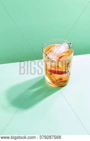 Sparkling Cold Brew Peach Tea With Thyme In Glass On Green Paper Background. Refreshing Summer Non-a