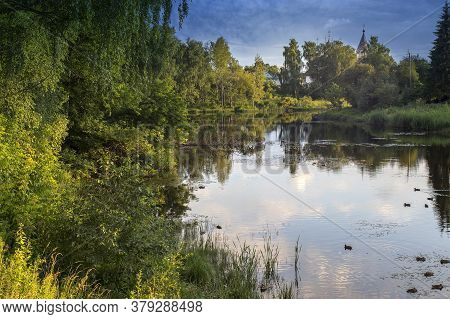 Reflections Of Clouds In A Village Pond Overgrown With Trees