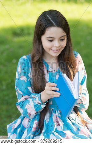 Child Girl Relaxing Outdoors With Book, New Chapter Concept.
