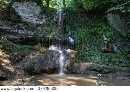 African Woman Climbs To The Water Of A Waterfall At A Hot Day In Summer. Linner Waterfall Is The Big