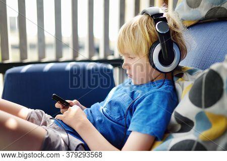 Preschooler Child Enjoy Listen Music Or Audiobook Using His Headphones At Home. Entertainment For Li