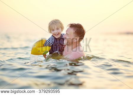 Preschooler Boy Wearing Inflatable Armbands And His Father Swimming On The Sea. Fun Beach Vacation F