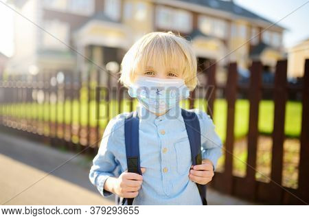 Child In Face Mask Going At Reopen School After Covid-19 Quarantine And Lockdown. It Is New Normal F