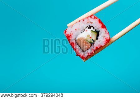 Tasty Sushi Roll Maki California With Wooden Chopsticks On Pink Background Close Up. Place For Capti
