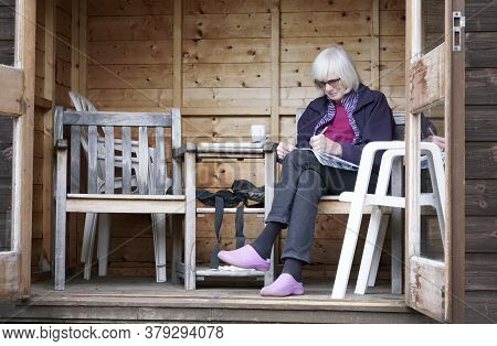 Senior Lady In Garden Shed Relaxing In Retirement