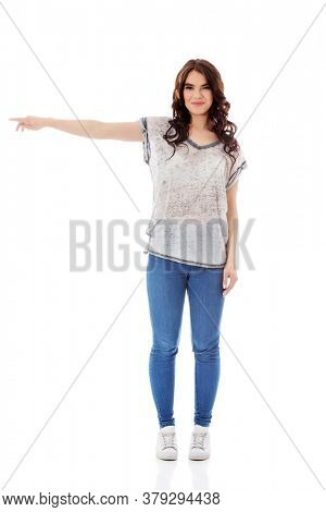 Young woman pointing to somewhere, isolated over a white background