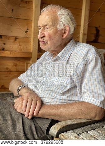 Senior Man In Garden Shed Relaxing In Retirement
