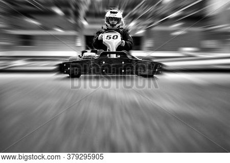 The Man Is Going On The Go-kart On Karting Track Indoors. He Is Wearing A Helmet. Black And White Im