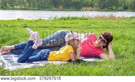 Little Girl In Nature, Having Fun Eating Chips. The Girl Has Fun Playing With Her Mother Against The