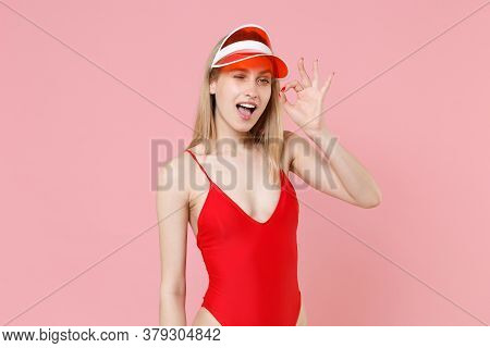 Funny Young Blonde Woman Girl In Red One-piece Swimsuit Cap Isolated On Pink Background Studio Portr