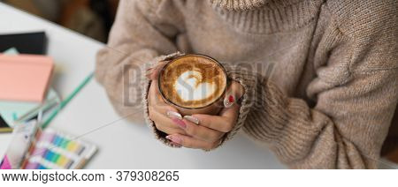 Top View Of Female Holding A Cup Of Beverage While Sitting At Worktable