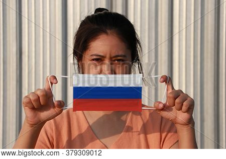 A Woman With Russia Flag On Hygienic Mask In Her Hand And Lifted Up The Front Face On Grey Backgroun