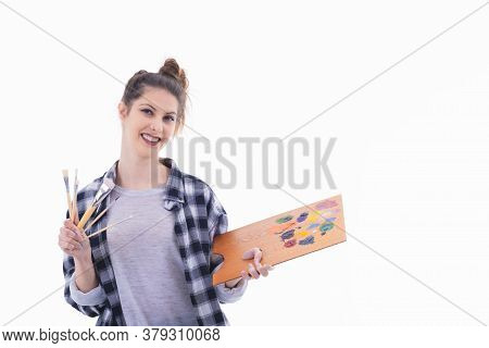 Beautiful Young Woman Holding A Painter Palette And An Assortment Of Paintbrushes