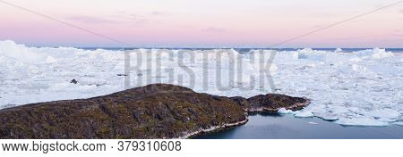 Greenland landscape nature with icebergs and ice in Greenland icefjord. Aerial drone panoramic banner photo of Ilulissat Icefjord with icebergs from Jakobshavn Glacier. Person in image for scale.