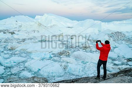 Travel in arctic landscape nature with icebergs. Greenland tourist man explorer taking photo with phone of amazing Greenland icefjord in Ilulissat affected by climate change and global warming.
