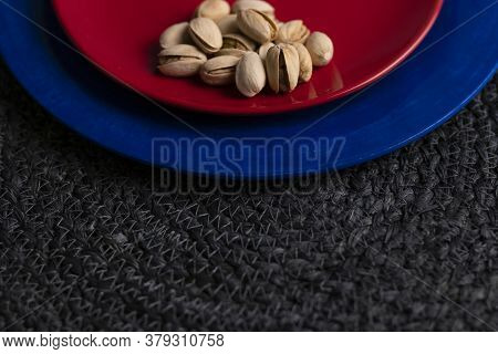 Raw Organic Pistachio Nuts Presented On A Red And Blue Plate