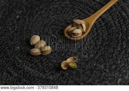 Raw Organic Pistachio Nuts Laid Out On Wooden Spoon