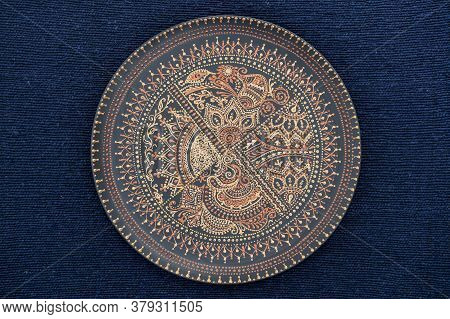 Decorative Ceramic Plate With Black And Golden Colors, Painted Plate On The Background Of Blue Fabri