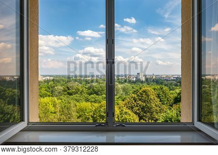 View from the open window at summer cityscape. Green park and residential districts view.