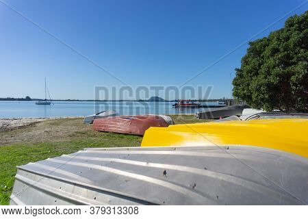 Omokoroa Waterfront With With Bright Yellow Hull Among Upturned Dinghies On Beach And Landmark Mount