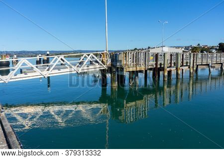Omokoroa Waterfront Pier With Structure Reflected In Calm Water.