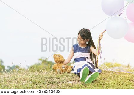 Happy Child Hug Teddy Bear Hold Air Balloon In Green Park Playground. Teddy Bear Best Friend For Lit