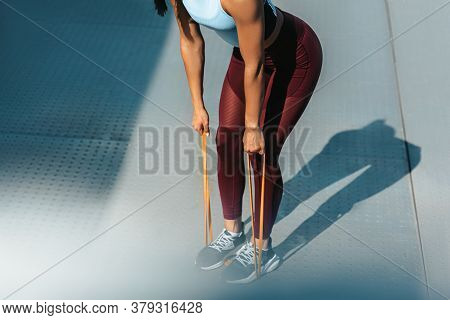Cropped Closeup Image Of Slim Fit Woman Exercising With Resistance Band On A Sunny Day Outdoor. Athe