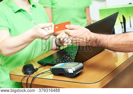 Cashier accepting credit card as payment for purchase
