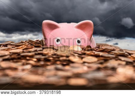 Pink piggy bank drowning in ocean of copper pennies with gathering storm clouds in background.