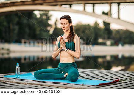 Sportswoman Meditating On Wooden Platform. Concept Of Healthy Lifestyle