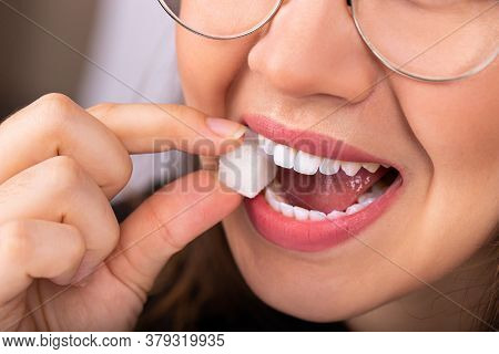 Beautiful Woman Mouth With Big White Teeth Bites On A White Sugar Cube