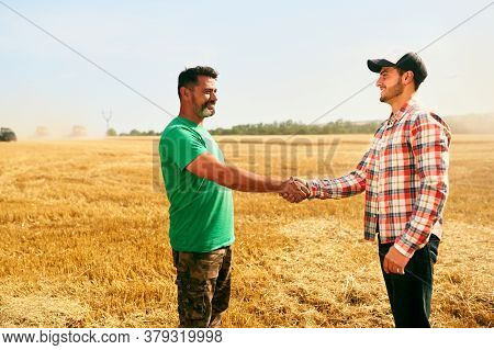 Farmer And Agronomist Shaking Hands In Wheat Field After Agreement. Agriculture Business Contract Co