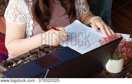 Woman's Hand Holding Red Pen Over Blurred Paperwork On Table Along With  Laptop