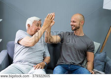 Happy Grandpa Giving High Five To His Grandson