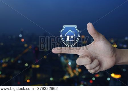 Hand Pressing House With Shield Flat Icon Over Blur Colourful Night Light City Tower And Skyscraper,