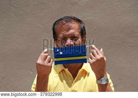 A Man With Curacao Flag On Hygienic Mask In His Hand And Lifted Up The Front Face. Tiny Particle Or