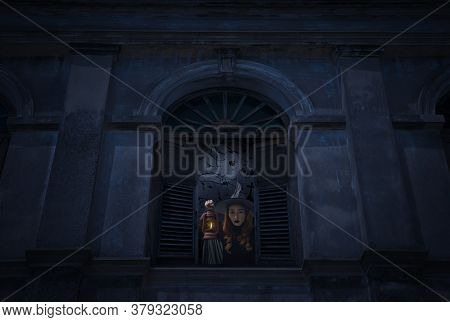 Halloween Witch Holding Ancient Lamp Standing In Old Damaged Window With Wall Over Cross, Church, Bi
