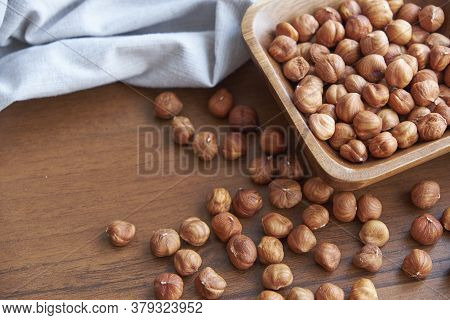 Hazelnut Kernels And Whole Hazelnuts On Old Brown Table, Selective Focus.