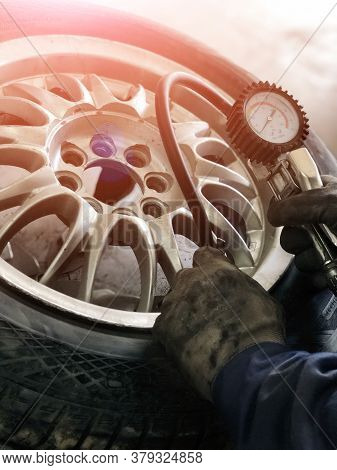 Auto Mechanic Man With Electric Screwdriver Changing Tire Outside. Car Service.  Tire Installation C