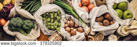 Zero waste concept. Eco bags with fruits and vegetables, glass jars with beans, lentils, pasta. Eco-friendly shopping and cooking concept, flat lay, copy space