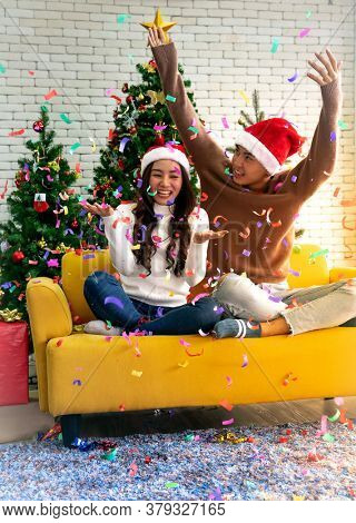 Young asian adult teenager couple celebrateing christmas holiday together in living room with christmas tree decoration.